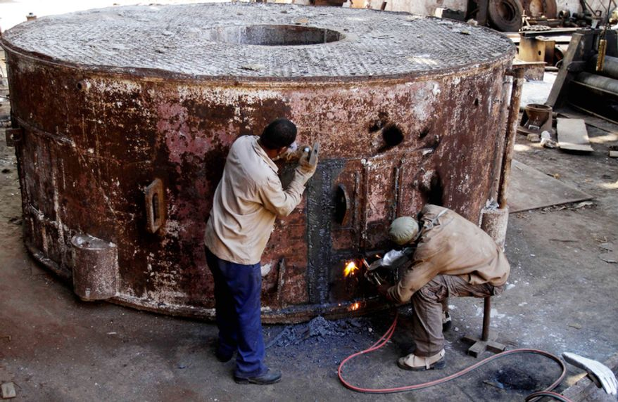 Juan Penalver (right), 52, and Jorge Luis Piss, 39, repair a boiler where sugar cane syrup is cooked at the Brasil sugar processing plant in Jaronu, Cuba. The plant, launched in 1921, is getting a makeover and expected to be ready in time for the upcoming annual harvest and to start milling cane by February 2013. (Associated Press)