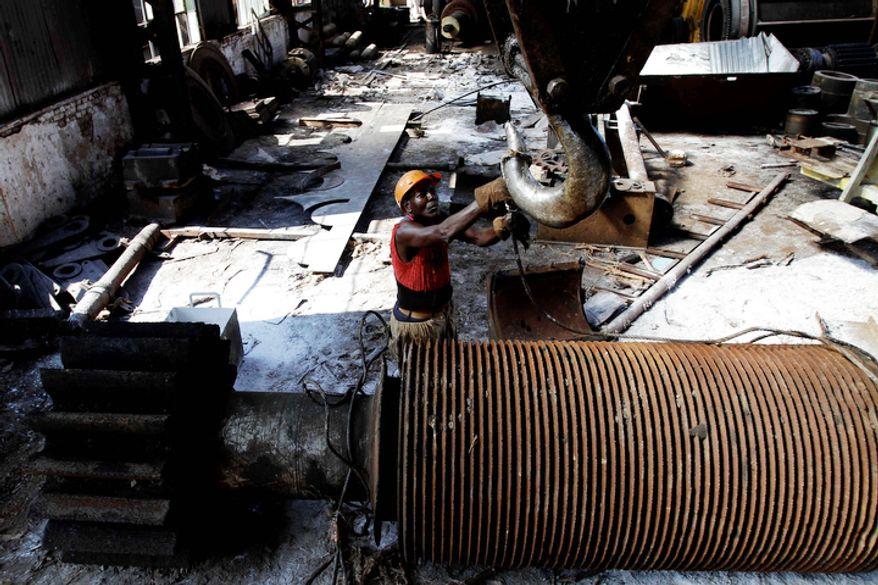 Jose Tabio, 56, repairs machinery at the Brasil sugar processing plant in Jaronu, Cuba. (Associated Press)