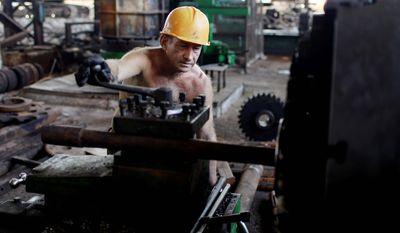 Aristeo Manzano, 58, repairs machinery at the Brasil sugar processing plant in Jaronu, Cuba. (Associated Press)