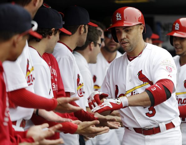 St. Louis Cardinals' Carlos Beltran (3) is congratulated by teammates in the dugout after hitting a two-run home run during the fourth inning of a baseball game against the Washington Nationals, Sunday, Sept. 30, 2012, in St. Louis. The home run was Beltran's second of the day. (AP Photo/Jeff Roberson)