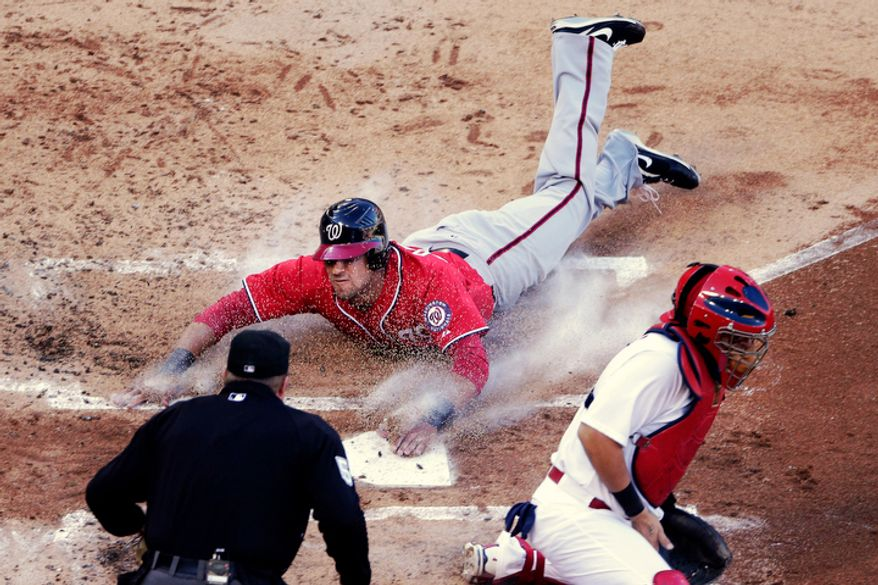 Washington Nationals' Ian Desmond, top, slides home past St. Louis Cardinals catcher Yadier Molina, bottom right, to score on a single by Jordan Zimmermann during the second inning of Game 2 in St. Louis. (AP Photo/Charlie Riedel)