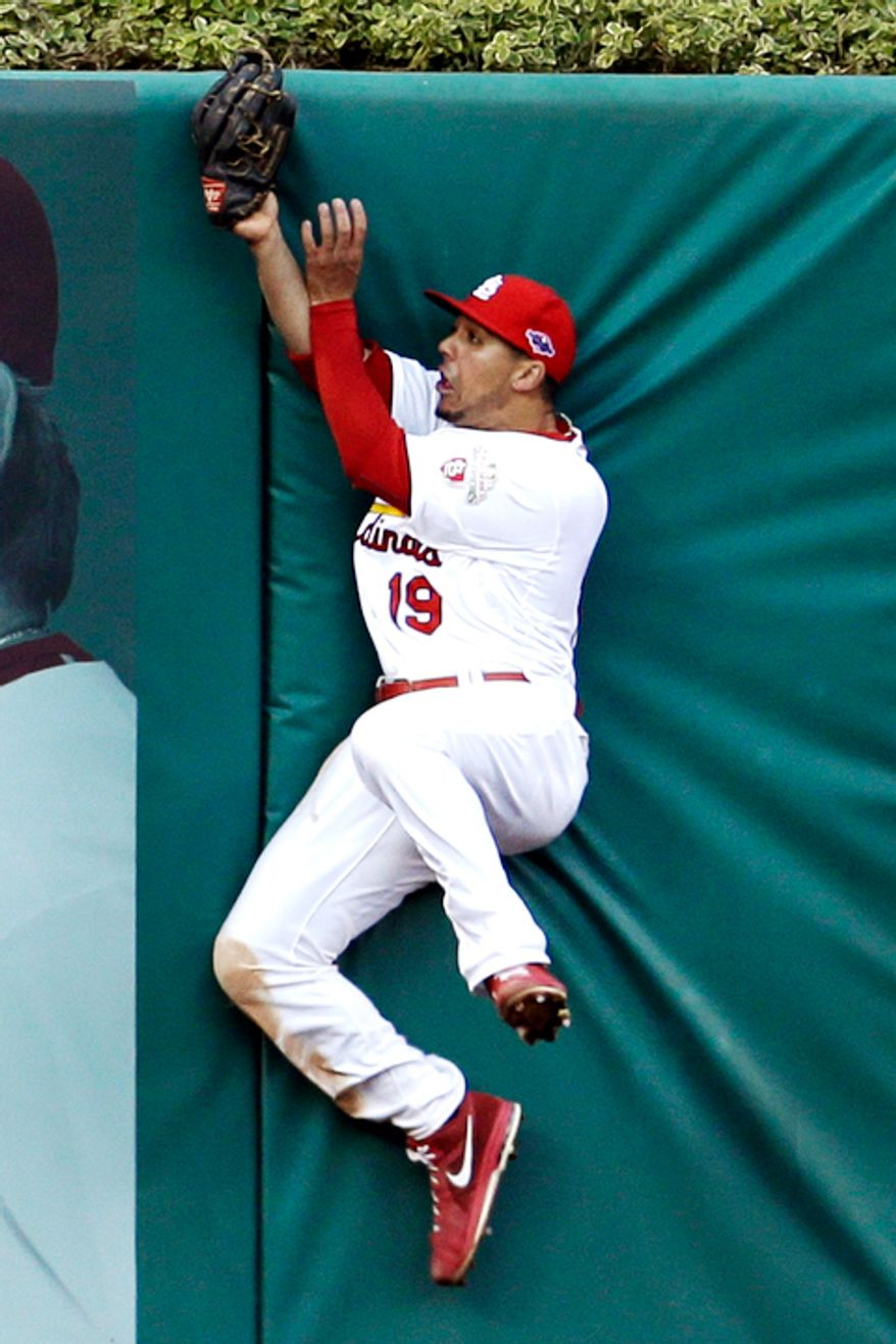 St. Louis Cardinals center fielder Jon Jay hits the outfield wall after catching a ball hit by Washington Nationals' Danny Espinosa for an out during the sixth inning in Game 2. (AP Photo/Jeff Roberson)