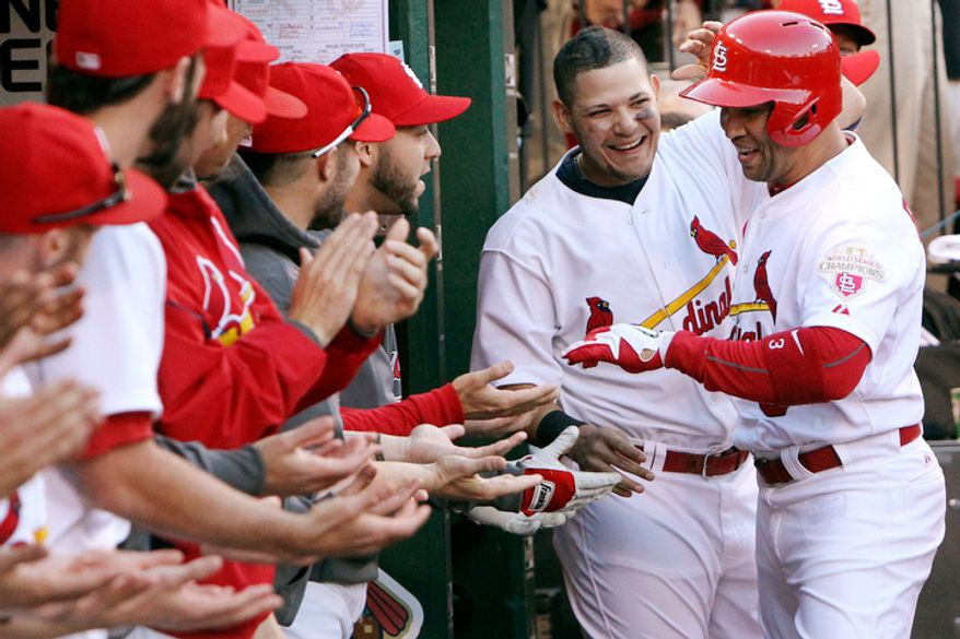 St. Louis Cardinals' Yadier Molina, second from right, congratulates Carlos Beltran after Beltran hit a solo home run against the Washington Nationals during the sixth inning of Game 2. (AP Photo/St. Louis Post-Dispatch, Chris Lee)
