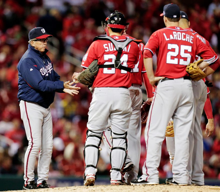 Washington Nationals manager Davey Johnson, left, makes a pitching change during the eighth inning of Game 2. (AP Photo/Charlie Riedel)
