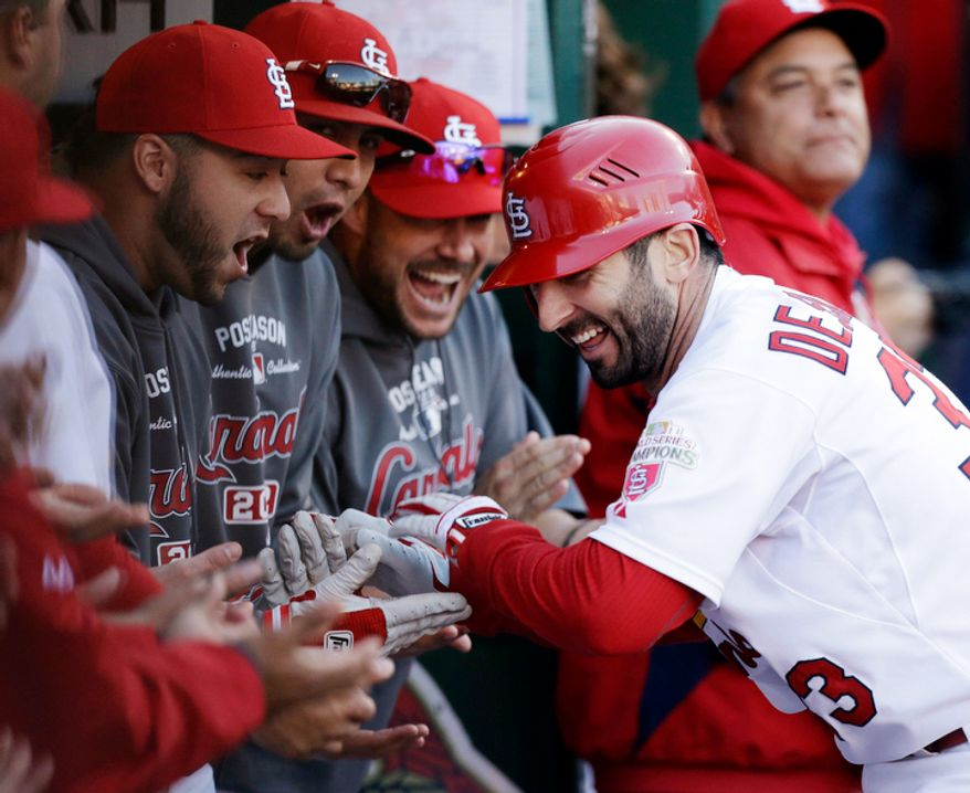 St. Louis Cardinals' Daniel Descalso celebrates with teammates in the dugout after hitting a solo home run against the Washington Nationals during the fourth inning of Game 2 of the National League division baseball series, Monday, Oct. 8, 2012, in St. Louis. The Cardinals won 12-4. (AP Photo/St. Louis Post-Dispatch, Chris Lee)