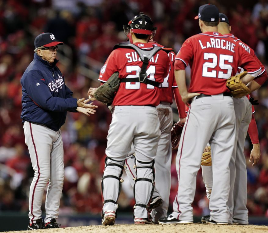 Washington Nationals manager Davey Johnson, left, makes a pitching change during the eighth inning of Game 2 of the National League division baseball series against the St. Louis Cardinals, Monday, Oct. 8, 2012, in St. Louis. The Cardinals won 12-4. (AP Photo/Charlie Riedel)