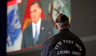 Vietnam veteran David Snyder of Metamora, Ohio, watches a live video broadcast of Republican presidential candidate Mitt Romney during a campaign event with Mr. Romney's running mate, Rep. Paul Ryan, on Monday, Oct. 8, 2012, in Swanton, Ohio. (AP Photo/Mary Altaffer)
