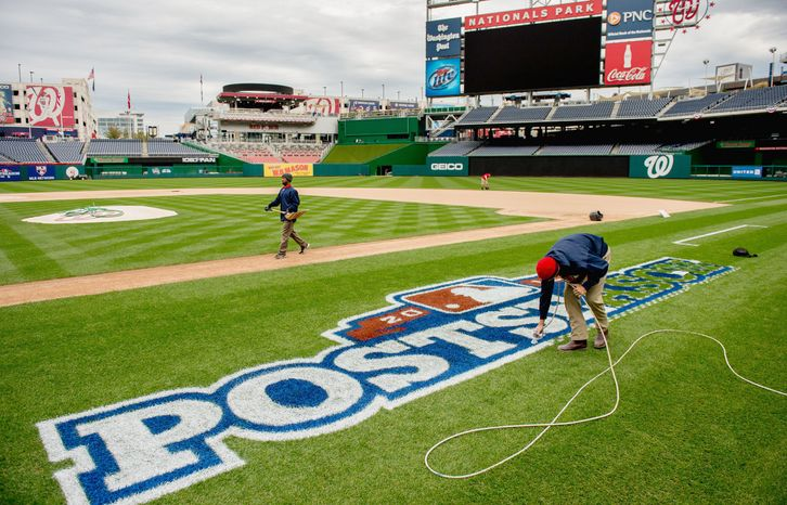 Mike Hrivnak airbrushes a special logo along the first-base line as he and the grounds crew get Nationals Park ready for its postseason debut Wednesday. The crew also switched out logos, touched up paint and added graphics for TV. (Andrew Harnik/The Washington Times)