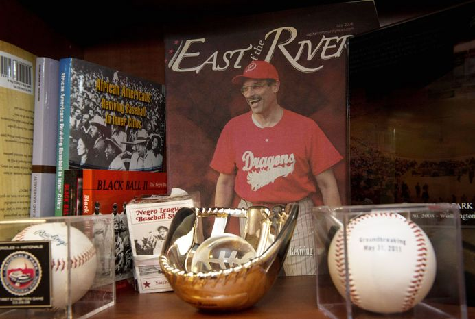 Baseball books and memorabilia fill shelves in the office of D.C. Mayor Vincent C. Gray, a lifelong fan of the game and standout player at Dunbar High School who vividly remembers attending Senators games at Griffith Stadium. (Rod Lamkey Jr./The Washington Times)
