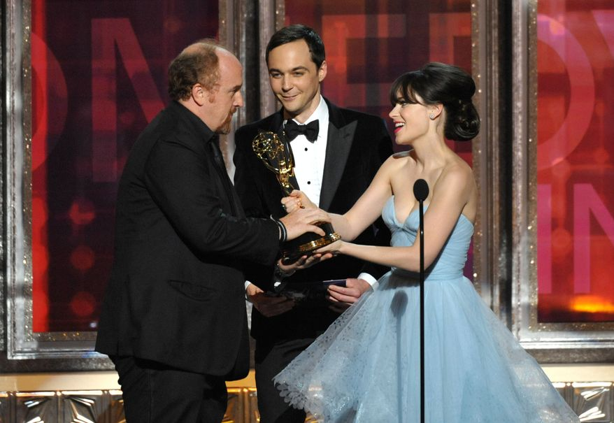 Louis C.K. (left) receives the Emmy for outstanding writing in a comedy series from Jim Parsons and Zooey Deschanel at the 64th Primetime Emmy Awards on Sunday, Sept. 23, 2012, in Los Angeles. (John Shearer/Invision/AP)