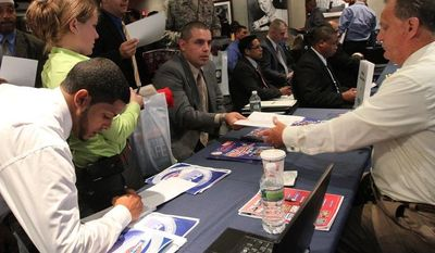 **FILE** Veteran Luis Gomez (seated center), 40, from Dover, N.J., hands his resume to a representative from White Rose Foods during a Sept. 28, 2012, job fair at Yankee Stadium in the Bronx borough of New York. (Associated Press)