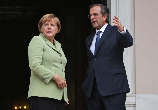 Greek Prime Minister Antonis Samaras (right) and German Chancellor Angela Merkel speak before their meeting at the Maximos mansion in Athens on Tuesday, Oct. 9, 2012. (AP Photo/Thanassis Stavrakis, Pool)