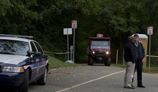 A police transport vehicle drives up the path where a body has been found off the trail in Thaiss Memorial Park in Fairfax, Va. on Monday, Oct. 8, 2012. Fairfax County Police have not yet determined if it is the body of missing 17-year-old W.T. Woodson High School student Bryan Glenn, who was last seen Oct. 1 when he dropped his brother off at school and whose car was found in the park's parking lot the next day. A search party set out near 10 a.m. this morning, and a small group later found the body. (Barbara L. Salisbury/The Washington Times)
