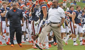 Virginia head coach Mike London cheers his team after a successfull goal line stand during the first half of the NCAA college football game at Scott stadium in Charlottesville, Va., Saturday, Sept. 29, 2012.   (AP Photo/Steve Helber)