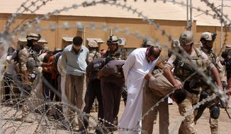 Blindfolded and handcuffed suspected al Qaeda members are led away to detention centers in an Iraqi army base in Hillah, Iraq, about 60 miles south of Baghdad, on Friday, July 20, 2012. (AP Photo/Alaa al-Marjani)