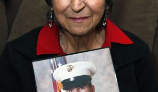 Delouise Guerra of Denver holds a 1975 photo of her younger brother, 18-year-old Marine PFC James Jacques, who was killed in a helicopter crash near Cambodia in 1975. (AP Photo/Ed Andrieski)