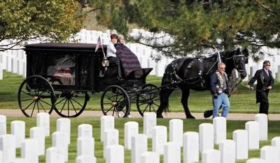A horse drawn carriage carries the casket and remains at funeral services for Marine PFC James Jacques at Fort Logan National Cemetery in Denver.  The funeral was held 37 years after he was killed during the rescue of the crew of an American cargo ship seized by Cambodia in May of 1975.  (AP Photo/Ed Andrieski)