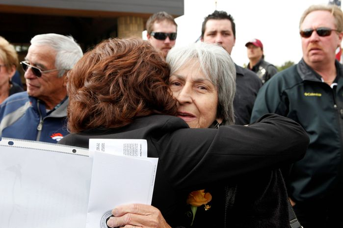 Delouise Guerra, right,  the sister of Marine  PFC James Jacques is hugged by a family member after his funeral at Fort Logan National Cemetery in Denver. (AP Photo/Ed Andrieski)