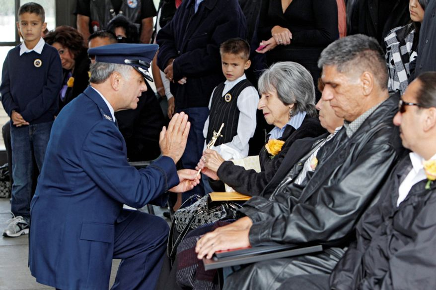 USAFA Chaplain Colonel Robert Bruno, left, presents a crucifix to Delouise Guerra the sister of Marine  PFC James Jacques during his funeral at Fort Logan National Cemetery in Denver. The Jacques funeral was held 37 years after he was killed during the rescue of the crew of an American cargo ship seized by Cambodia in May of 1975. His remains were identified in August 2012. (AP Photo/Ed Andrieski)