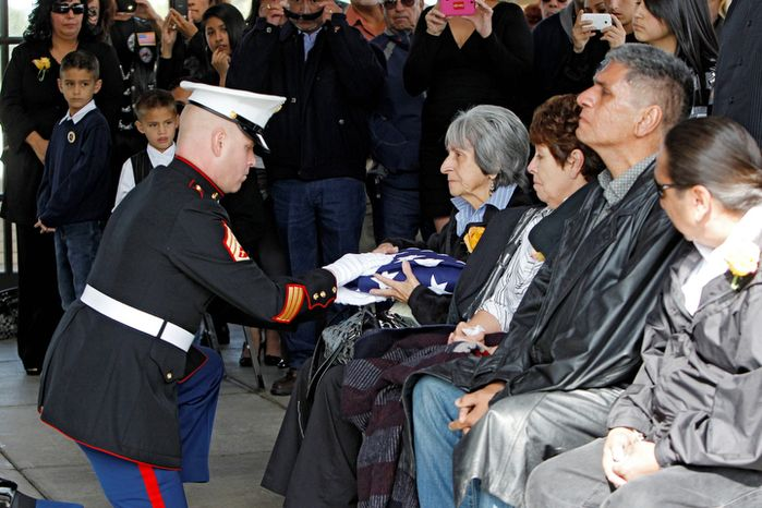 Delouise Guerra the sister of Marine  PFC James Jacques is presented the flag that draped his casket at Fort Logan National Cemetery in Denver on Tuesday, Oct. 9, 2012.  (AP Photo/Ed Andrieski)