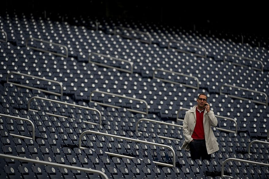 ** FILE ** Saint Louis Cardinals vice president and general manager John Mozeliak talks on the phone in the stands while his team takes to the field to practice at Nationals Park on Tuesday, Oct. 9, 2012. (Barbara L. Salisbury/The Washington Times)