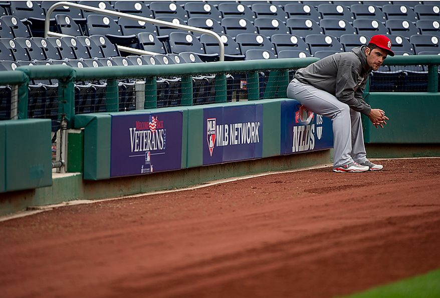 Saint Louis Cardinals player Jaime Garcia, who pitched for two innings in Monday's game before acknowleding a broken arm, watches on the sidelines while his team work outs at Nationals Park on Tuesday, Oct. 9, 2012. On Wednesday, they play the St. Louis Cardinals at home. (Barbara L. Salisbury/The Washington Times)