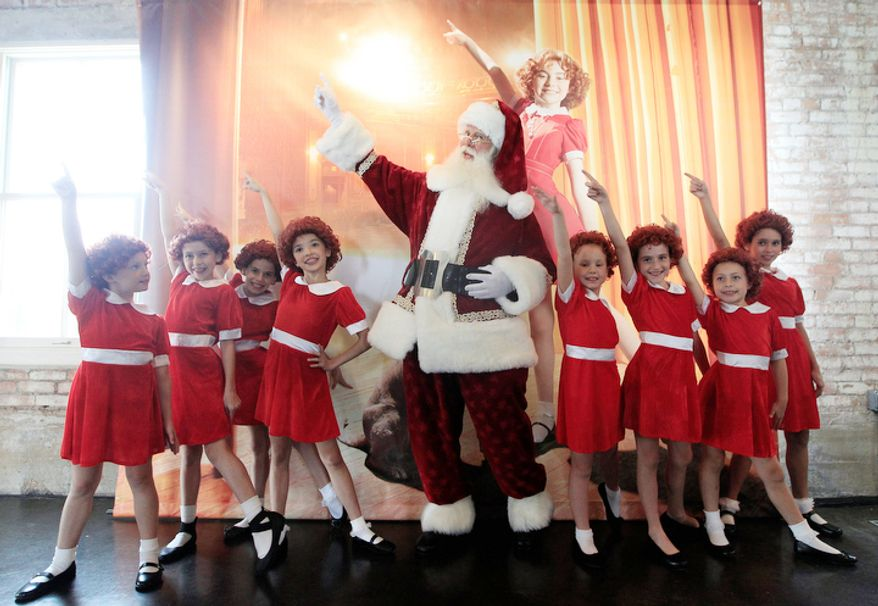 With several Annies on hand, Brady White portrays Santa Claus, center, as he and the little actresses display the a gift Annie:The Musical Walk-on Role during the unveiling of the Neiman Marcus 2012 Christmas Book in Dallas, Tuesday, Oct. 9, 2012. For $30,000, the gift buys a walk on role in the Broadway musical.  (AP Photo/LM Otero)