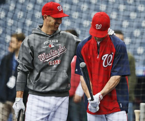 Adam LaRoche jokes around with Bryce Harper during the Nationals workout Tuesday, a day before Game 3 of the NLDS against the Cardinals. (Associated Press)