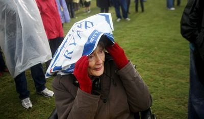 Gladys Plympton, 91, shields herself from the rain before Republican presidential candidate Mitt Romney takes the stage for a campaign stop on Monday, Oct. 8, 2012, in Newport News, Va. (AP Photo/Jason Hirschfeld)