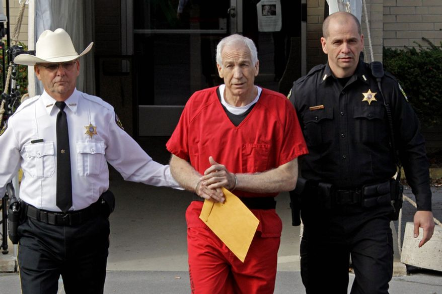Former Penn State University assistant football coach Jerry Sandusky (center) is escorted Oct. 9, 2012, by police as he leaves the Centre County Courthouse after being sentenced in Bellefonte, Pa. (Associated Press)