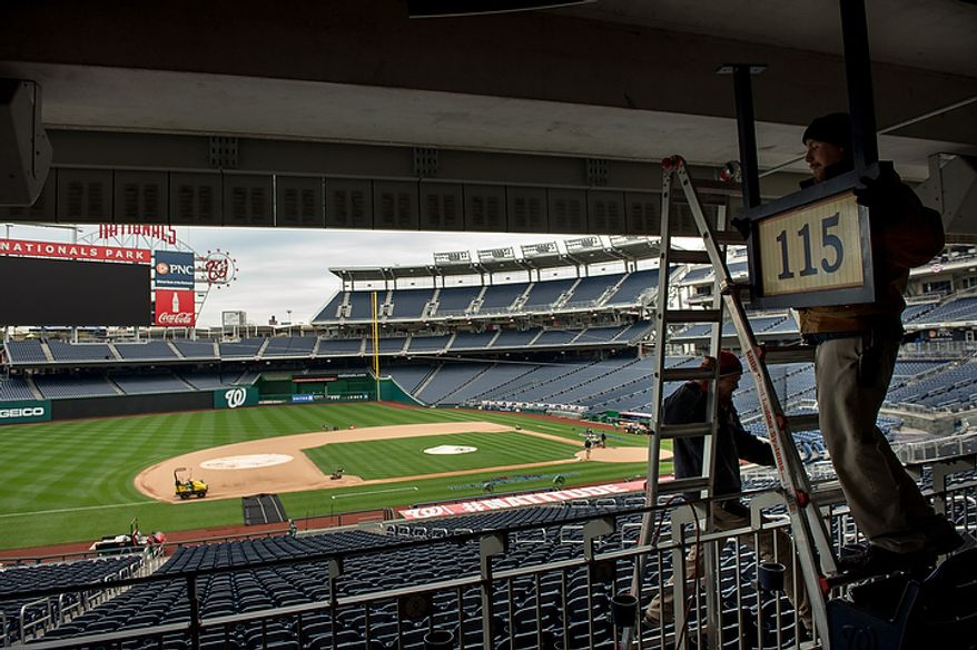 Stadium workers Peter Gabauer, right, and Wes Snyder, bottom left, take down a sign to make way for an extra camera platform along the third base stands as crews get ready for game 3 at Nationals Park as the Washington Nationals take on the St. Louis Cardinals in the first round of the Major League Baseball playoffs, Washington, D.C., Monday, October 8, 2012. (Andrew Harnik/The Washington Times)