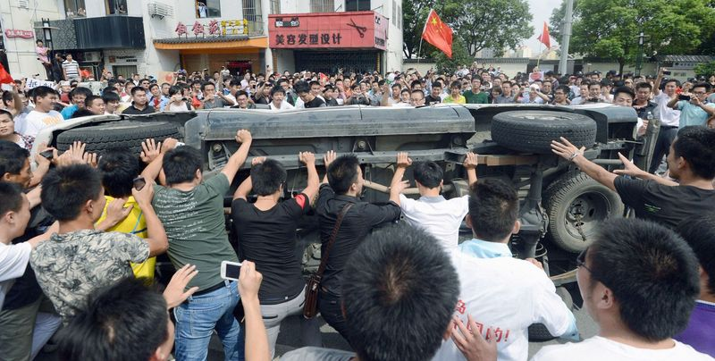 Anti-Japan demonstrators overturn a Japanese-made car in Suzhou, China, last month after Japan nationalized islands that both nations claim but Japan controls. Sales of Japanese-made vehicles nose-dived in China, and a new report predicts a 70 percent drop October through December. (The Associated Press)