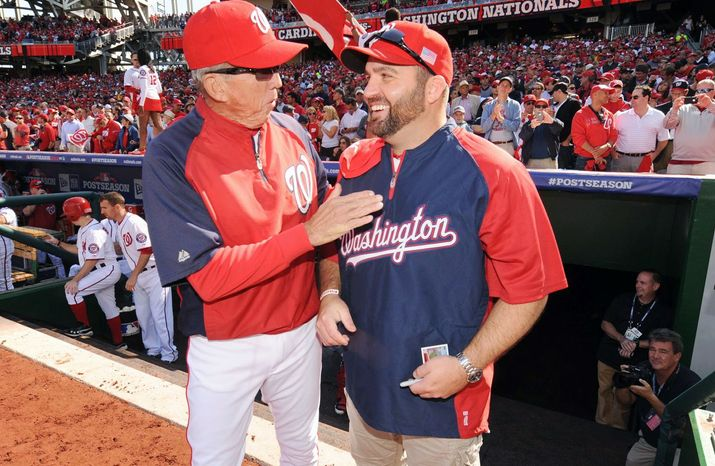 Army Staff Sgt. Brian Keaton, here with Washington Nationals manager Davey Johnson, delivered the lineup card to home plate Wednesday before the Washington Nationals played the St. Louis Cardinals in Game 3 of the National League Division Series at Nationals Park. Sgt. Keaton is recovering from wounds he sustained in Iraq. (Washington Nationals)