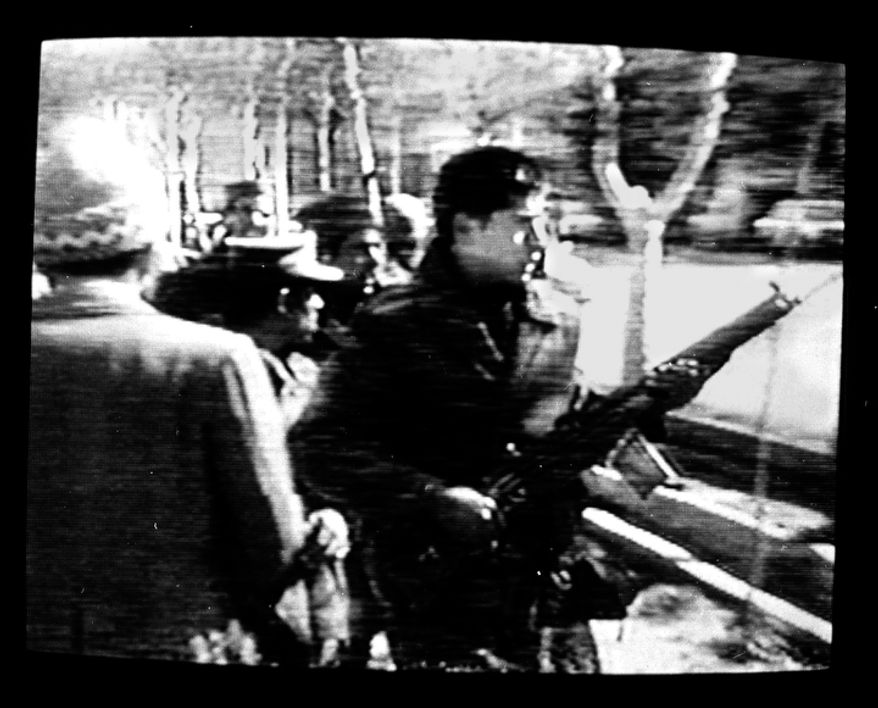 A man carries an assault rifle during the storming of the U.S. Embassy in downtown Tehran, Iran, Feb. 14, 1979.  Ambassador William Sullivan and 101 other Americans were taken hostage. Photo was made from a television monitor showing CBS-TV. (AP Photo/Suzanne Vlamis)