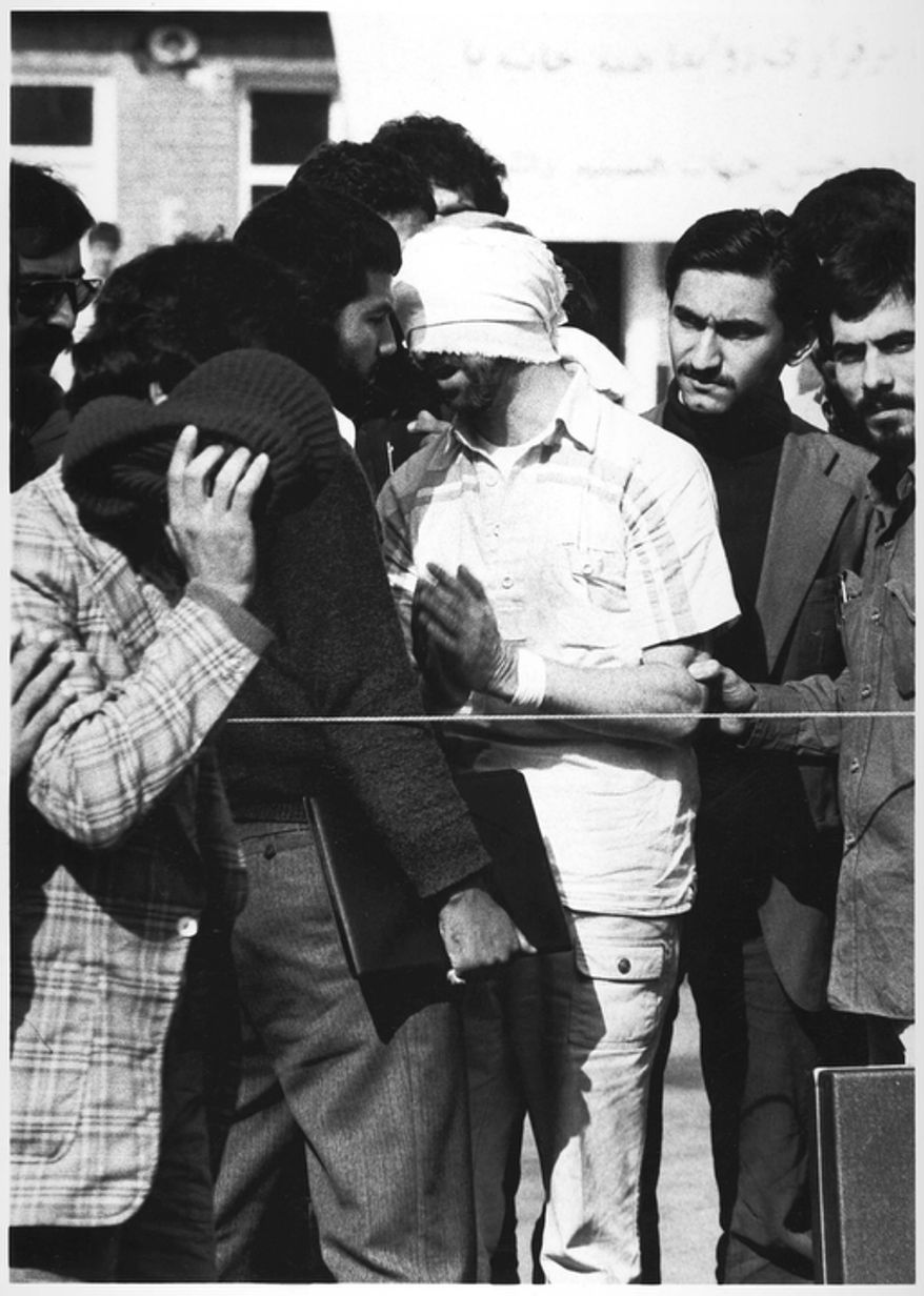 One of 60 U.S. hostages, blindfolded and with his hands bound, is being displayed to the crowd outside the U.S. Embassy in Tehran by Iranian hostage takers.  (AP Photo)