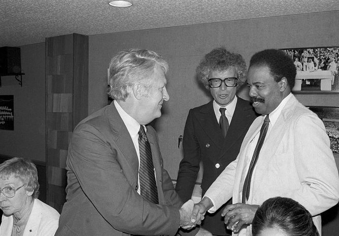 United States Ambassador to the United Nations, Donald McHenry, right, shakes hands with Bob Anders, one of the Americans secreted out of Iran by former Canadian Ambassador to Iran Ken Taylor, center, in New York, May 30, 1980. The three attended a dinner before New York Yankees Canadian Night at Yankee Stadium.  (AP Photo/Richard Drew)