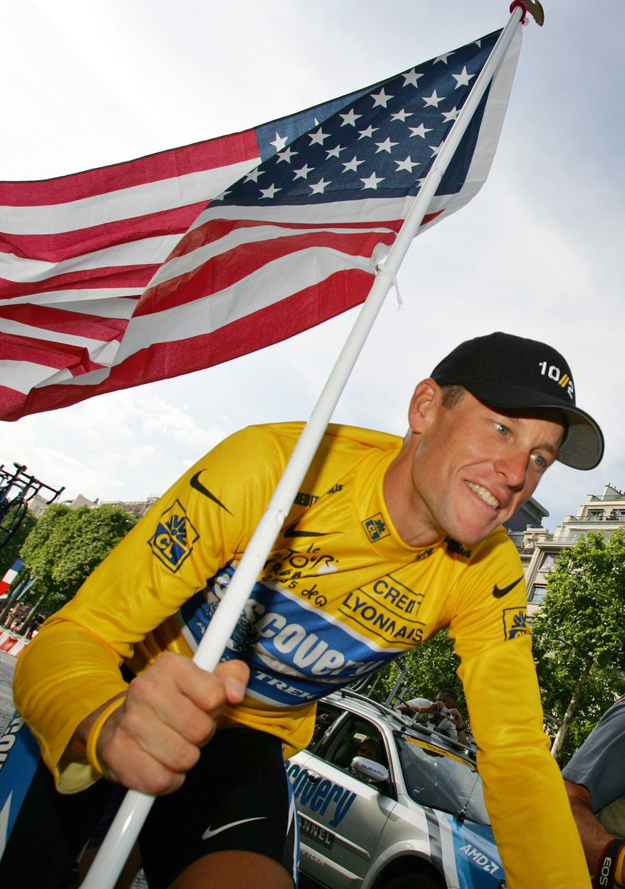 **FILE** Lance Armstrong carries the United States flag during a victory parade on the Champs Elysees avenue in Paris on July 24, 2005, after winning his seventh straight Tour de France cycling race. (Associated Press)