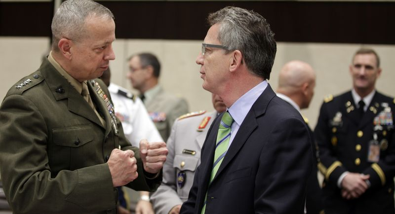 U.S. Marine Gen. John Allen (left), the top commander in Afghanistan, speaks with German Defense Minister Thomas de Maiziere during a round-table meeting of NATO defense ministers at the alliance's headquarters in Brussels on Wednesday, Oct. 10, 2012. (AP Photo/Virginia Mayo)