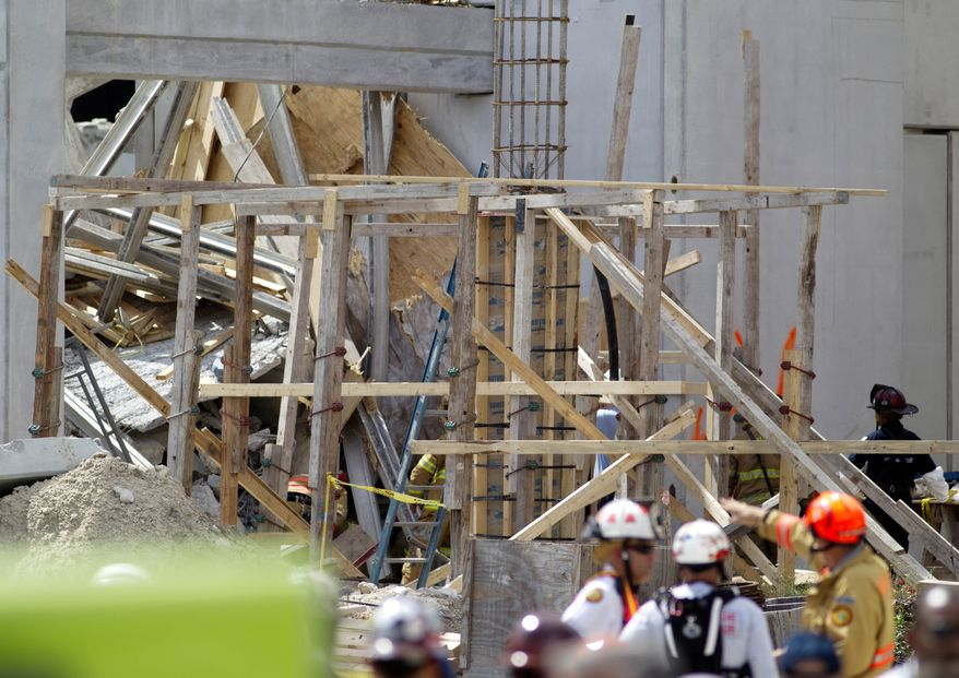 Firefighters examine the rubble Oct. 10, 2012, after a section of a parking garage under construction at Miami-Dade College in Doral, Fla., collapsed, killing one worker and trapping at least two others. (Associated Press)