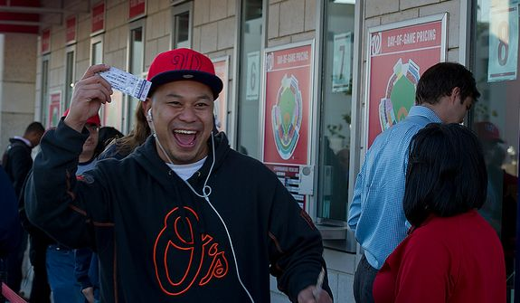David Chheng of Herndon, Va. smiles as he holds up his ticket for the first home playoff game at Nationals Park on Wednesday, Oct. 10, 2012. He got to the stadium at 8:35 and paid $30 for the standing-room-only seat. He says he also follows the Orioles (thus the sweatshirt), and would love to see the two teams play one another. (Barbara L. Salisbury/The Washington Times)