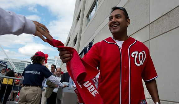 "A Washington Nationals fan takes his free ""Natitude"" towel as he walks into Nationals Park for the first home game in the National League Division Series on Wednesday, Oct. 10, 2012. The franchise had some 40,000 of the towels made for fans who attended Wednesday's game. (Barbara L. Salisbury/The Washington Times)"
