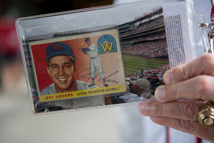 A Washington Nationals fan holds up his 1955 Roy Sievers baseball card on Wednesday, Oct. 10, 2012 during the National League Division Series game at Nationals Park. (Barbara L. Salisbury/The Washington Times)