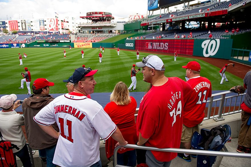 Tom O'Brien of Owen, Md., left, and Wil Yow of Woodbridge, Va., right, watch warms ups before the Washington Nationals play the St. Louis Cardinals in game three of Major League Baseball playoffs at Nationals Park, Washington, D.C., Wednesday, October 10, 2012. (Andrew Harnik/The Washington Times)