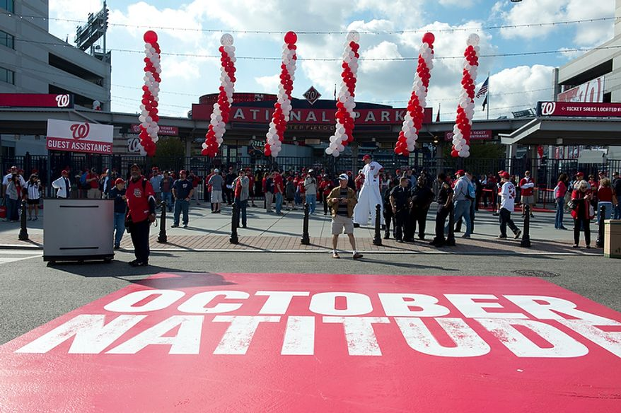 "Fans gather outside of Nationals Park in Washington, D.C., on Wednesday, Oct. 10, 2012 for the Nationals' first home playoff game. The words ""October Natitude"" have been painted on the street in front of the Center Gate Field. (Barbara L. Salisbury/The Washington Times)"
