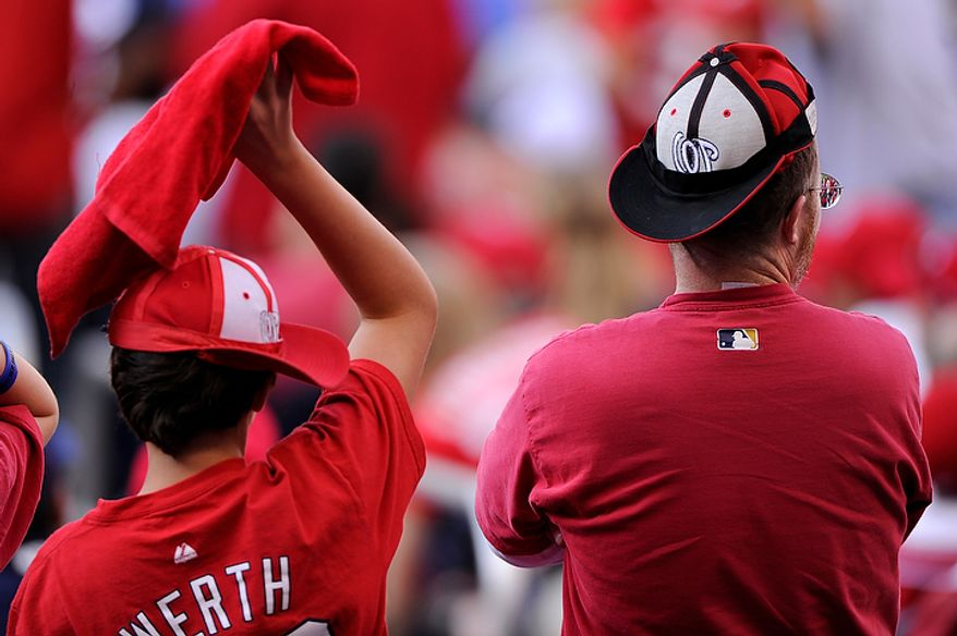 Brennan Willmott-McMahon (L) and Jonathan Willmott, from Alexandria, Va., sport rally caps in the bottom of the 9th to no avail, as the Washington Nationals would go on to lose to the St. Louis Cardinals 8-0 in Game 3 of the National League Division Series at Nationals Park, Washington, D.C.., Oct. 10, 2012. (Preston Keres/Special to The Washington Times)