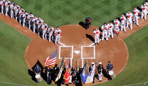 Players from the St. Louis Cardinals and the Washington Nationals stand during the National Anthem before Game 3 of the National League Division Series at Nationals Park, Washington, D.C., Oct. 10, 2012. (Preston Keres/Special to The Washington Times)