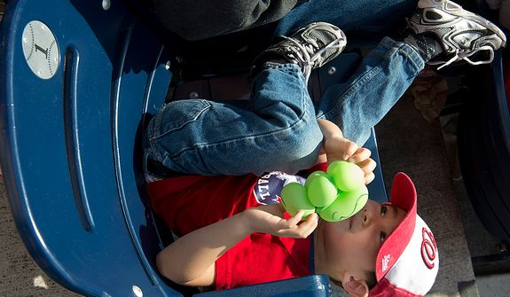 Nicholas Argow, 4, of Alexandria, Va. plays in his seat in the outfield at Nationals Park during the third game of the National League Division Series against the St. Louis Cardinals on Wednesday, Oct. 10, 2012. (Barbara L. Salisbury/The Washington Times)