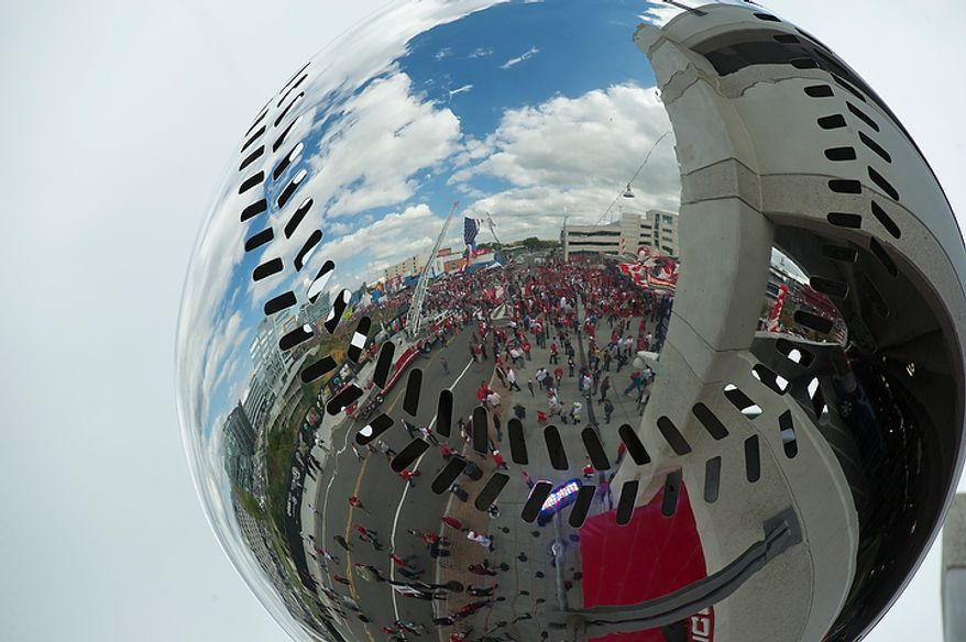 The crowd outside Nationals Park is seen reflected in one of the silver baseballs that hang outside the ticket office before the start of game three of the National League Division Series against the St. Louis Cardinals on Wednesday, Oct. 10, 2012. (Barbara L. Salisbury/The Washington Times)