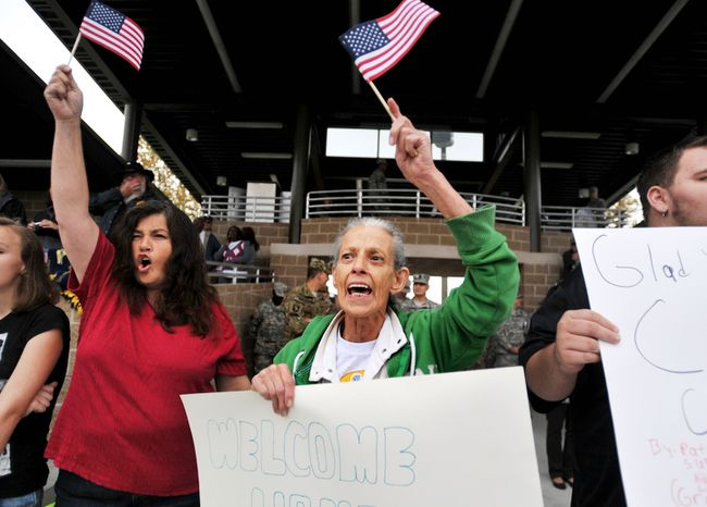 Wava Harmes, center, and her daughter Janette Surrell, left,  wave flags for SPC Curtis Hutton during a welcome home ceremony for soldiers from the Army's 1st Battalion, 30th Infantry Regiment, Wednesday, Oct. 10, 2012 at Fort Stewart, Ga.(AP Photo/Stephen Morton)