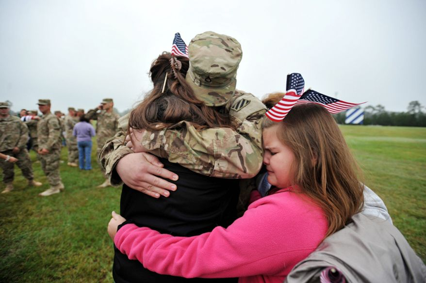 Army Pfc. Derek Southard, center, is hugged by his mother Shawn Southard, left, and his sister Jaylee Hepner, right, during a welcome home ceremony for soldiers from the Army's 1st Battalion, 30th Infantry Regiment, Wednesday, Oct. 10, 2012 at Fort Stewart, Ga.  (AP Photo/Stephen Morton)